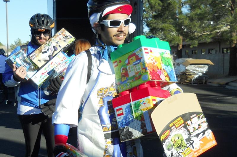 Braulio López Santamaría sobre la bici se apresta a regalar juguetes